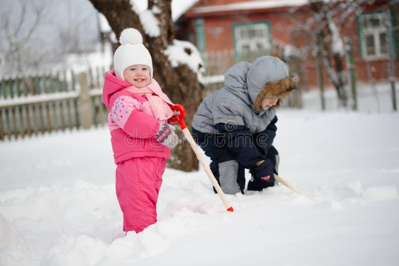 孩子扫清从雪的道路 图库摄影