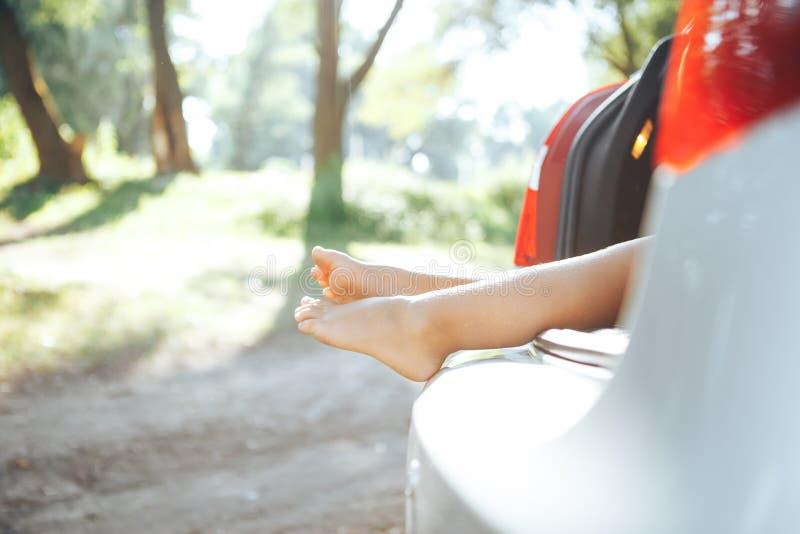 孩子投入了腿在树干外面 行李起动和孩子 愉快的暑假 免版税库存照片