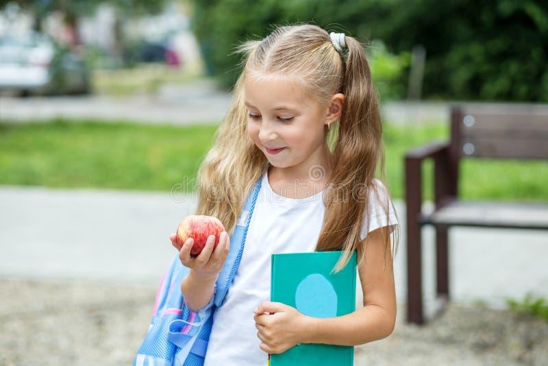 孩子拿着一本书和一个苹果 学校的概念,研究,教育,友谊,童年 免版税库存图片