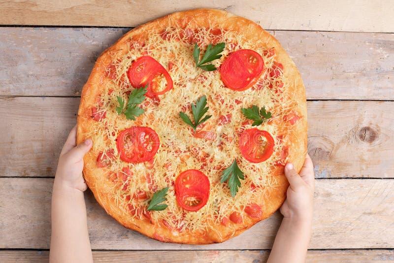 孩子拿着玛格丽塔比萨用蕃茄和两红色辣椒在灰色桌、顶视图和地方上文本的 库存图片