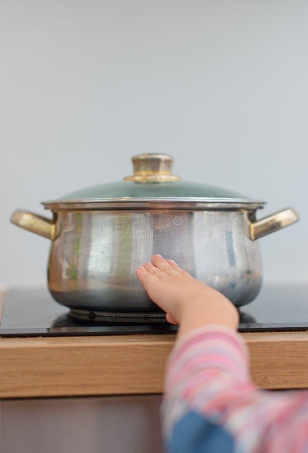 孩子接触在火炉的热的平底锅 库存照片
