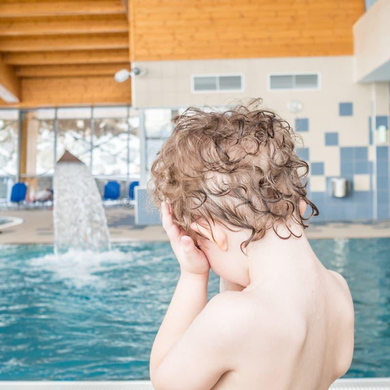 孩子掩藏他的眼睛用他的在游泳池旁边的手 免版税库存图片