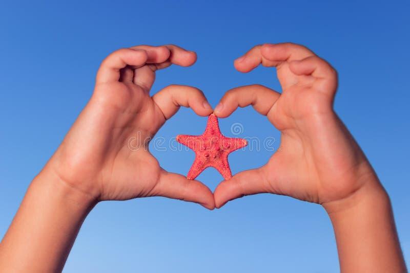 孩子握手由天空决定以与海星的心脏的形式 爱形状有海星的儿童手 库存图片