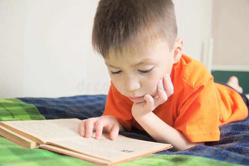 孩子教育,男孩说谎在床,儿童画象上的阅读书微笑与书,教育,有趣的故事书 免版税库存照片