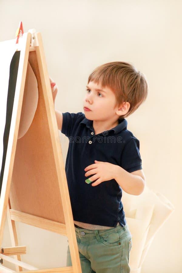 孩子是在家画和绘与在木画板艺术家画架纸的毛毡笔孩子和孩子的 ?? 库存照片