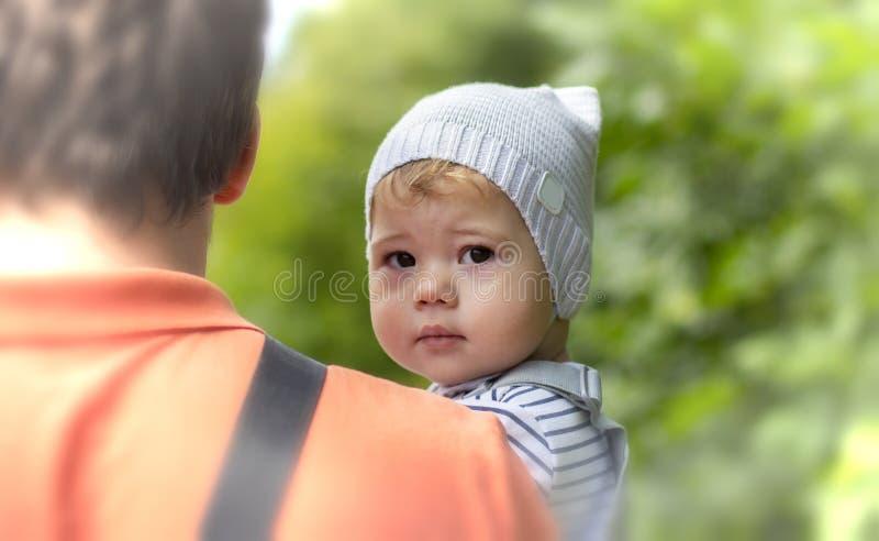 孩子是在爸爸的胳膊 帽子的一个男孩看在肩膀,当坐在他的父亲s胳膊时小孩女孩的画象 免版税图库摄影