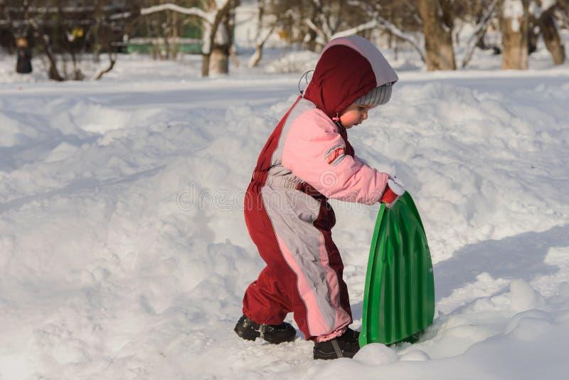 孩子是在雪撬的手里 免版税库存图片