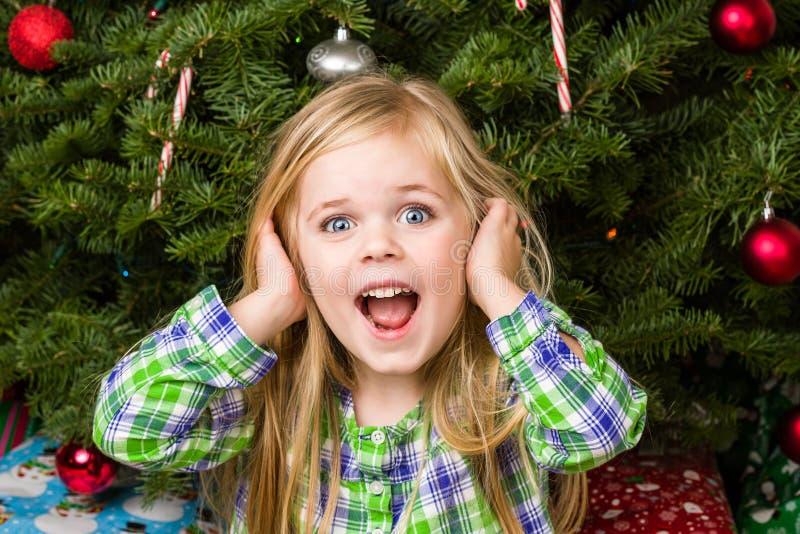 孩子是相当愉快的关于她的圣诞节 免版税库存照片