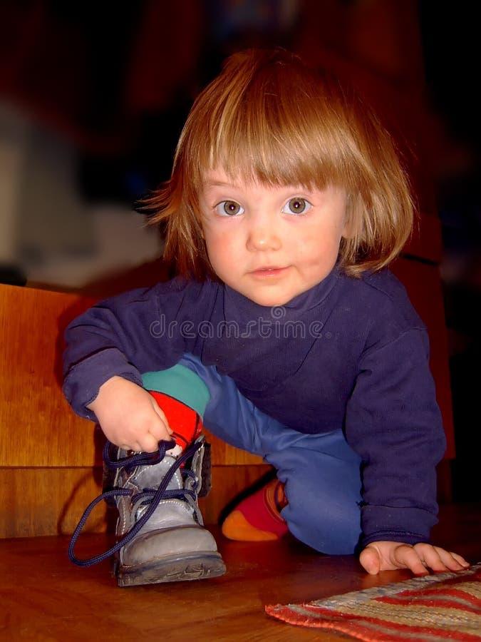 孩子是蹲和栓鞋带 库存图片