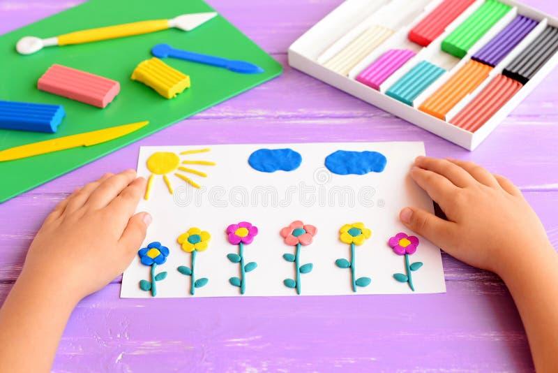 孩子显示与彩色塑泥花、太阳和云彩的一张卡片 儿童艺术工艺的供应在木桌上 雕塑黏土工艺 库存照片