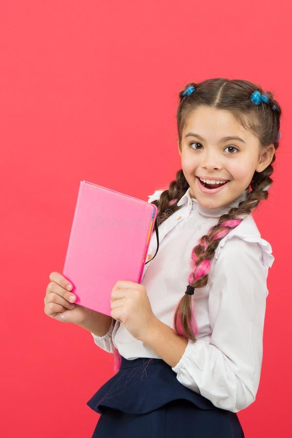 孩子校服举行书 文具钦佩者 女小学生展示笔记薄 学校用品概念 学校文具 库存照片