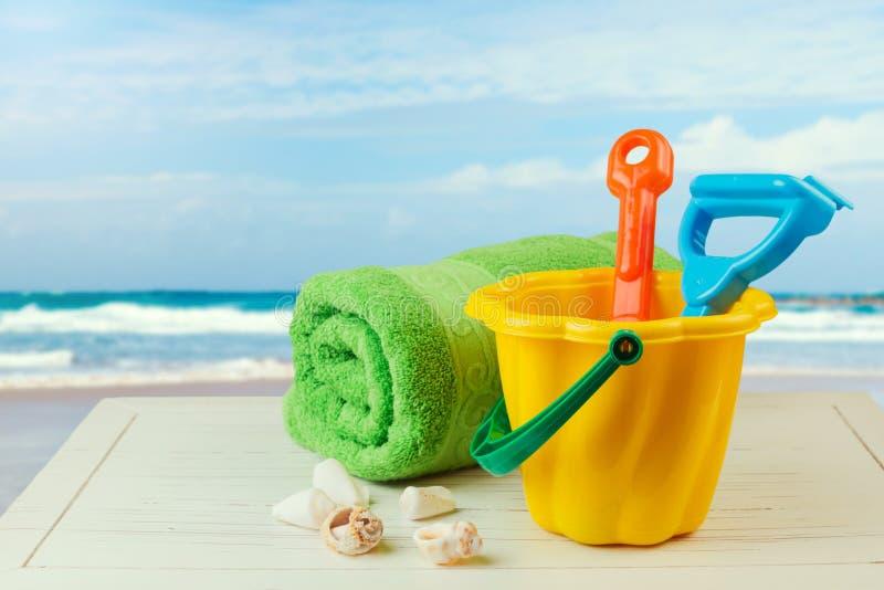 孩子桶和小铲为在海滩的松弛天 库存图片
