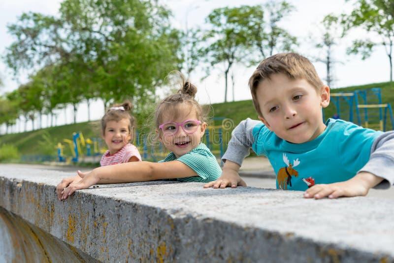 孩子正面图在城市公园、男孩和女孩的花费时间坐石头 愉快的微笑的爱恋的兄弟和姐妹 库存图片