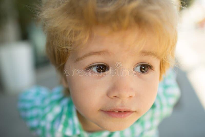 孩子注视接近  儿童画象 孩子面孔 滑稽的婴孩 漂亮的孩子概念面孔 免版税库存图片