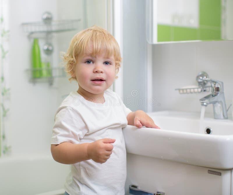 孩子洗涤的手在卫生间里 图库摄影