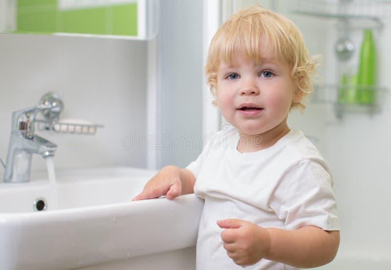 孩子洗涤的手在卫生间里 库存图片