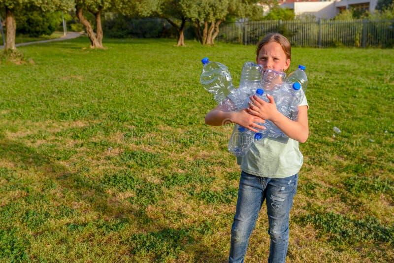 孩子清洁在公园 清扫废弃物的志愿少年女孩 免版税库存图片