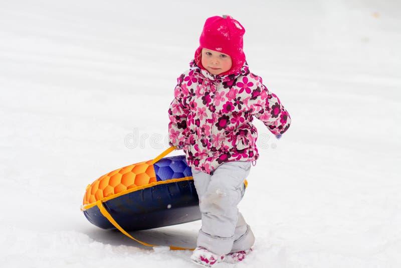 孩子滚动下来雪小山 库存图片