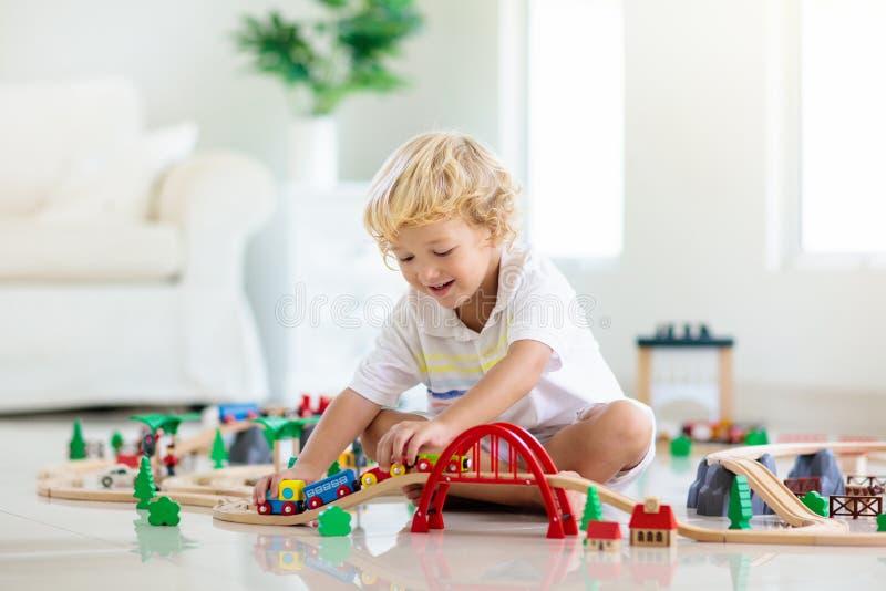 孩子演奏木铁路 有玩具火车的孩子 免版税图库摄影