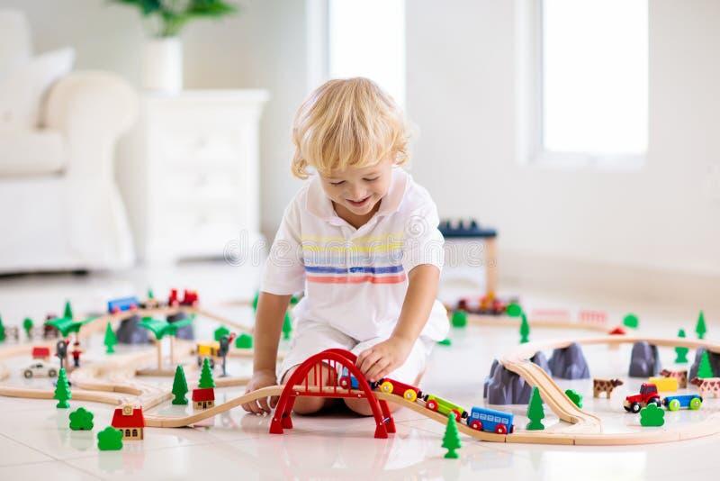 孩子演奏木铁路 有玩具火车的孩子 免版税库存图片