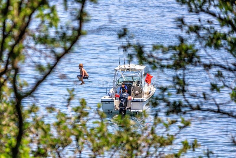 孩子潜水入从汽艇的海水由Cuacasus山黑海海岸  库存照片