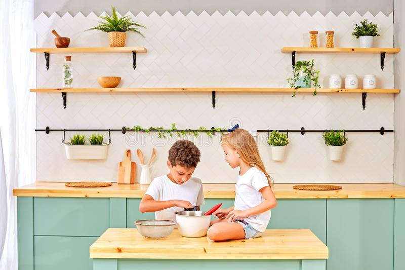 孩子烹调并且演奏用面粉和面团在厨房里 库存图片