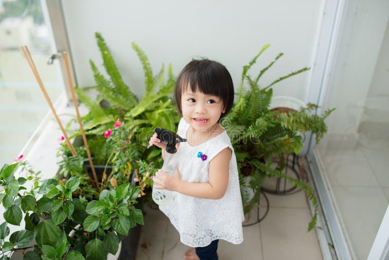 孩子照料植物 逗人喜爱的小女孩浇灌的第一spr 免版税图库摄影