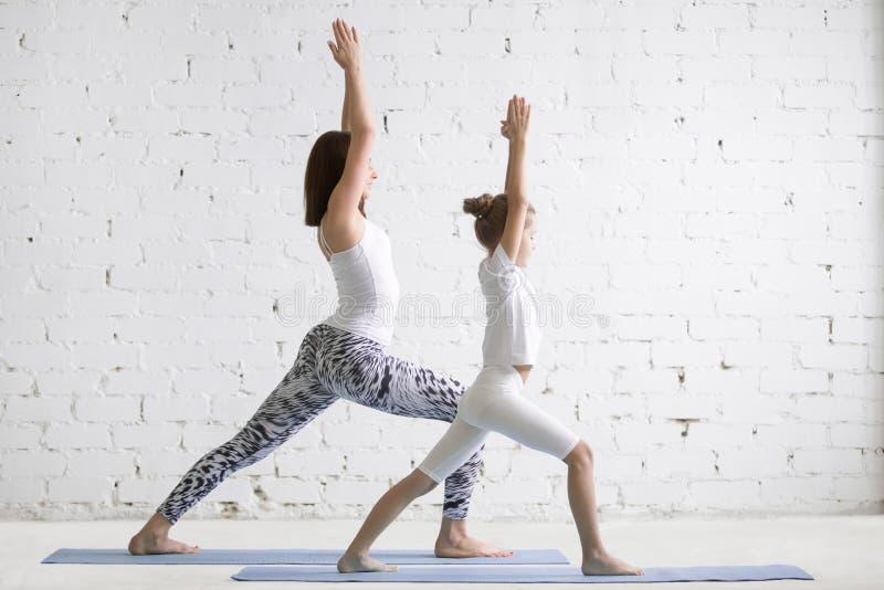 孩子瑜伽与女孩孩子的师范训练Virabhadrasana姿势 库存图片