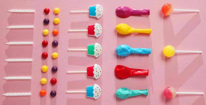 孩子生日宴会装饰,桃红色背景样式 五颜六色的糖果、明亮的气球、欢乐蜡烛和纸秸杆 库存照片