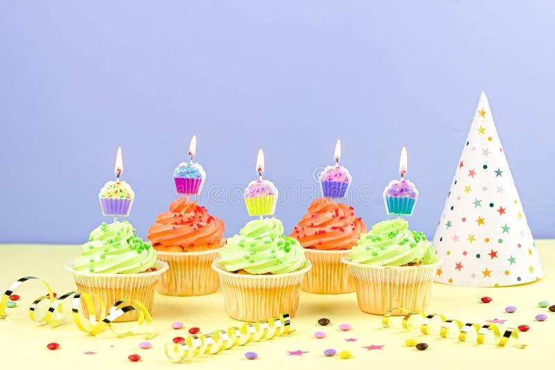 孩子生日宴会辅助部件-与灼烧的蜡烛,党帽子,飘带,五彩纸屑的五颜六色的杯形蛋糕 r 免版税库存照片