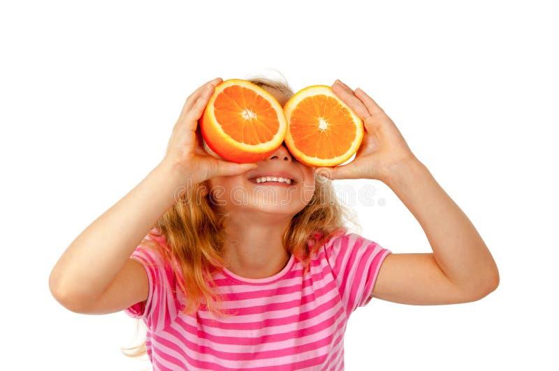 孩子用桔子 库存图片