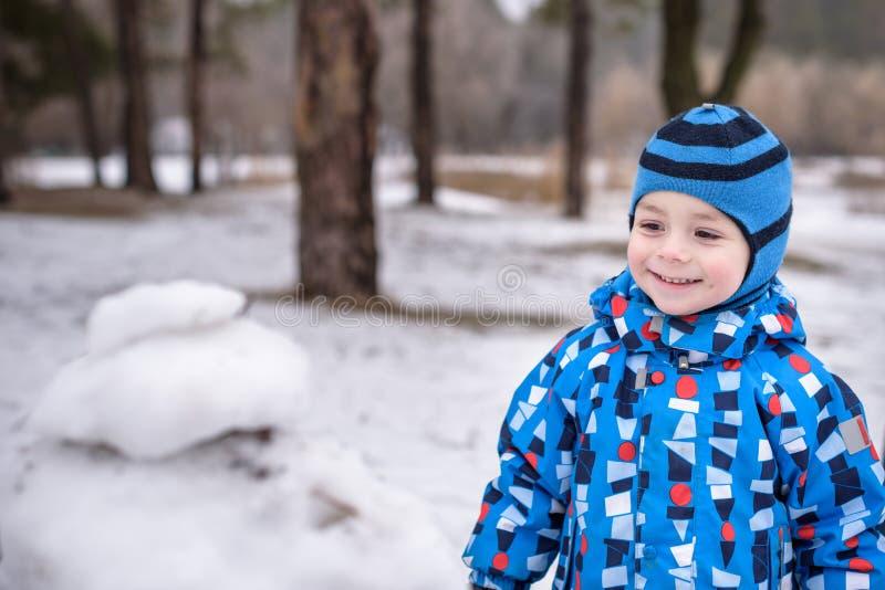 孩子男孩冬天画象五颜六色的衣裳的,户外在降雪期间 与孩子的活跃outoors休闲冷的多雪的d的 图库摄影