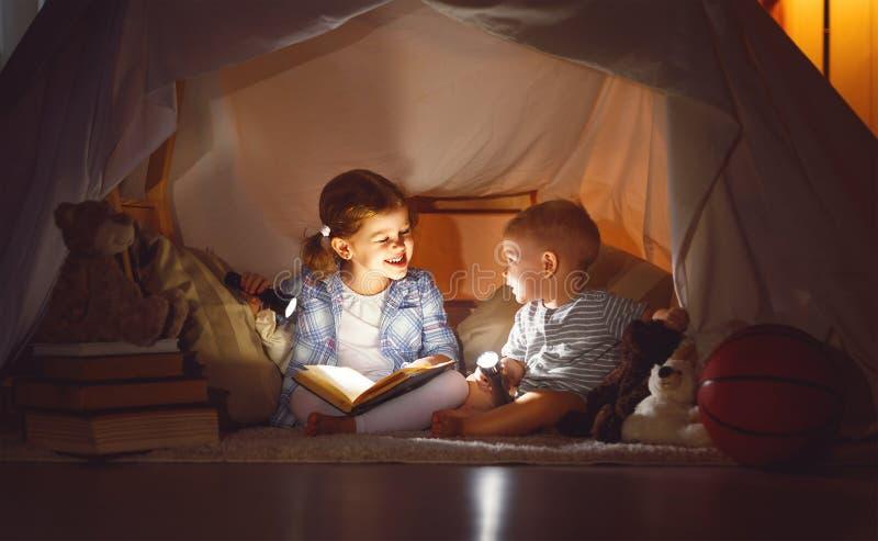 孩子男孩和女孩与手电的阅读书在帐篷 免版税库存图片