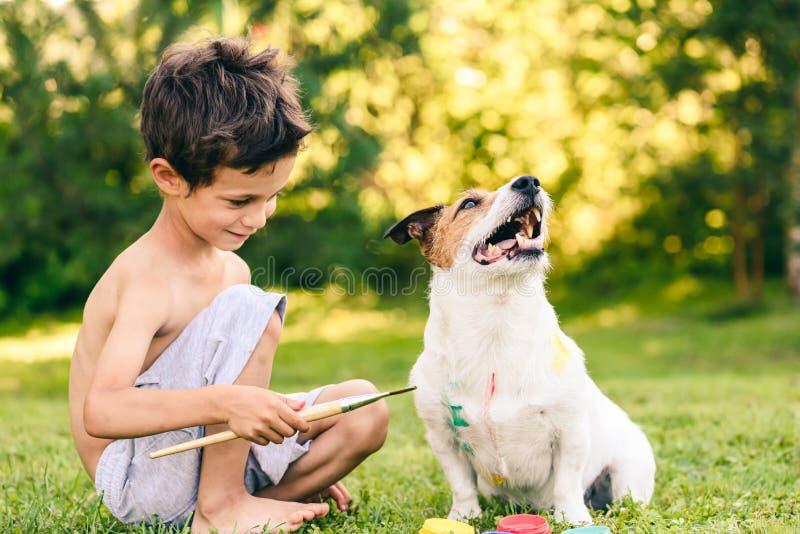 孩子男孩狗为在外套的狂欢节绘的构成做准备 库存照片