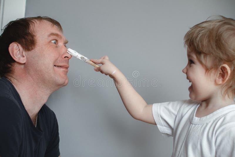 家庭的概念 孩子画在他的父亲的鼻子的一把刷子 获得的父亲和的女儿在家乐趣 免版税图库摄影