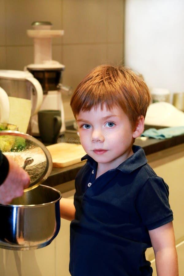 孩子画象在厨房里 逗人喜爱的小男孩,使用在厨房里 小孩饿,看并且检查是它完成的午餐 免版税库存照片