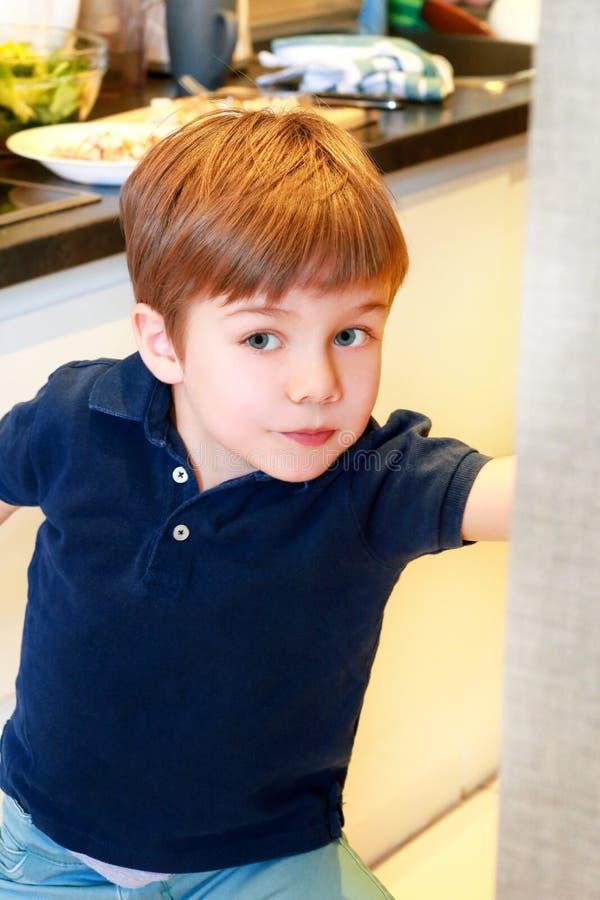 孩子画象在厨房里 逗人喜爱的小男孩,使用在厨房里 小孩饿,看并且检查是它完成的午餐 图库摄影