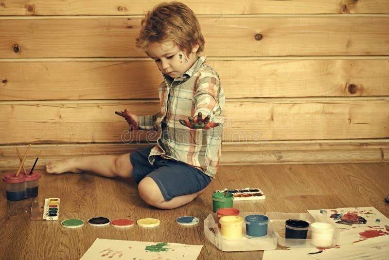 孩子画 孩子用色的手、树胶水彩画颜料油漆和图画 免版税库存照片