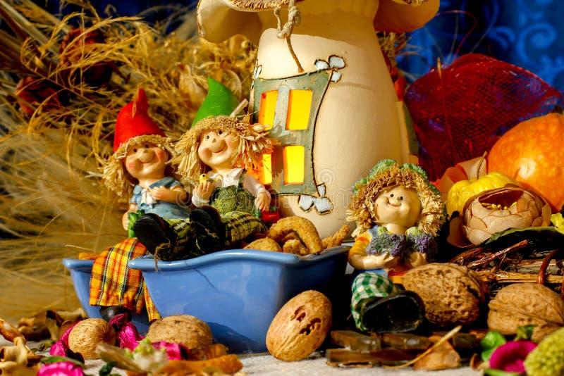 孩子的、快餐、干燥叶子、核桃和土气装饰美丽的构成iwith小雕象  免版税图库摄影