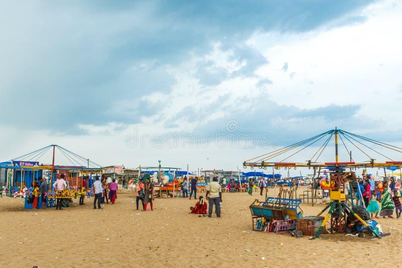 孩子的与蓝天,黑暗的云彩在背景中,小游艇船坞海滩,金奈,印度2017年8月19日被隔绝的木马乘驾放荡的人 免版税库存照片