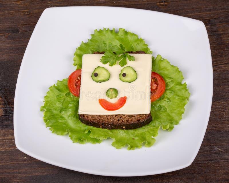 孩子的乐趣食物-在面包的面孔 库存图片