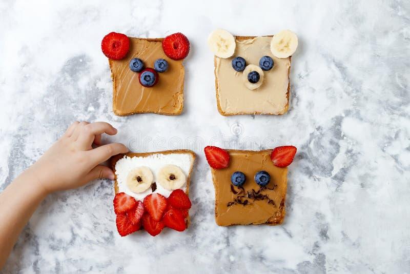 孩子的健康滑稽的面孔三明治 动物面对多士用花生和腰果黄油,乳清干酪,香蕉,草莓 免版税库存图片