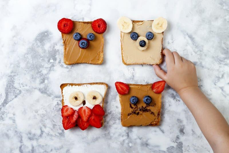 孩子的健康滑稽的面孔三明治 动物面对多士用花生和腰果黄油,乳清干酪,香蕉,草莓 库存图片