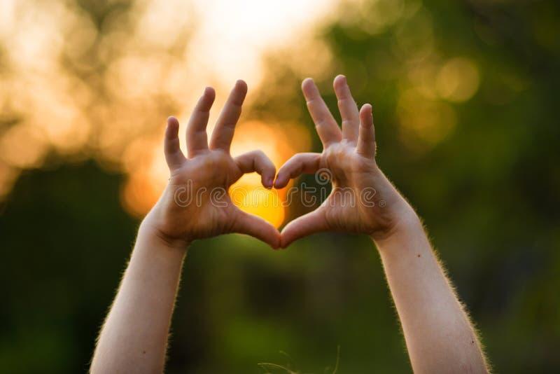 孩子的儿童的爱,仁慈,爱概念的肢体语言的心形手 在自然背景的心脏手 库存图片