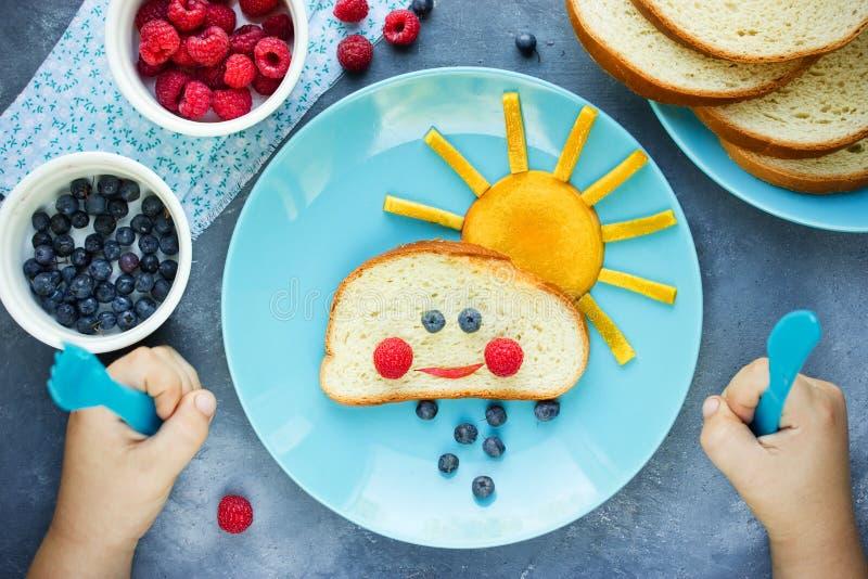 孩子的创造性的早餐想法-在小圆面包上添面包用果子和berr 免版税库存图片