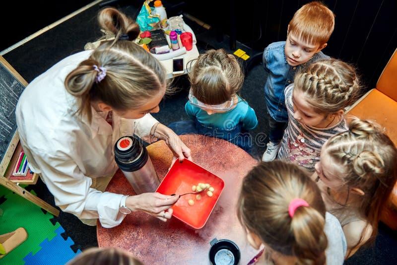孩子的化工展示 教授完成了与液氮的化工实验在生日女孩 免版税库存图片