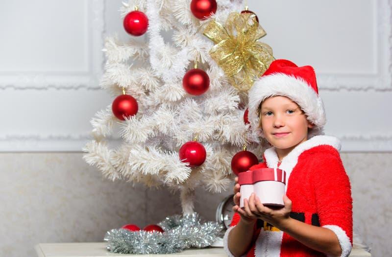 孩子的圣诞树想法 作为与红色帽子举行礼物盒的圣诞老人穿戴的男孩孩子在圣诞树附近 圣诞节圣诞老人 免版税库存图片