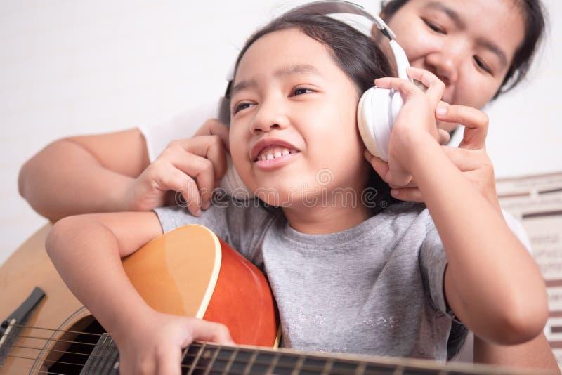 孩子的妇女佩带的白色耳机 库存照片