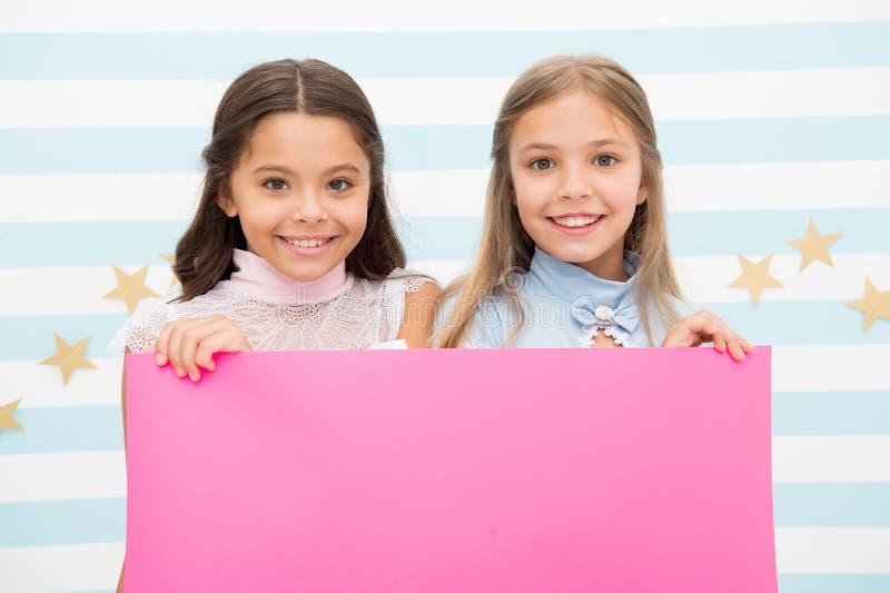 孩子的学校公告 您做广告这里 小女孩哄骗拿着学校公告的桃红色纸 桃红色 图库摄影