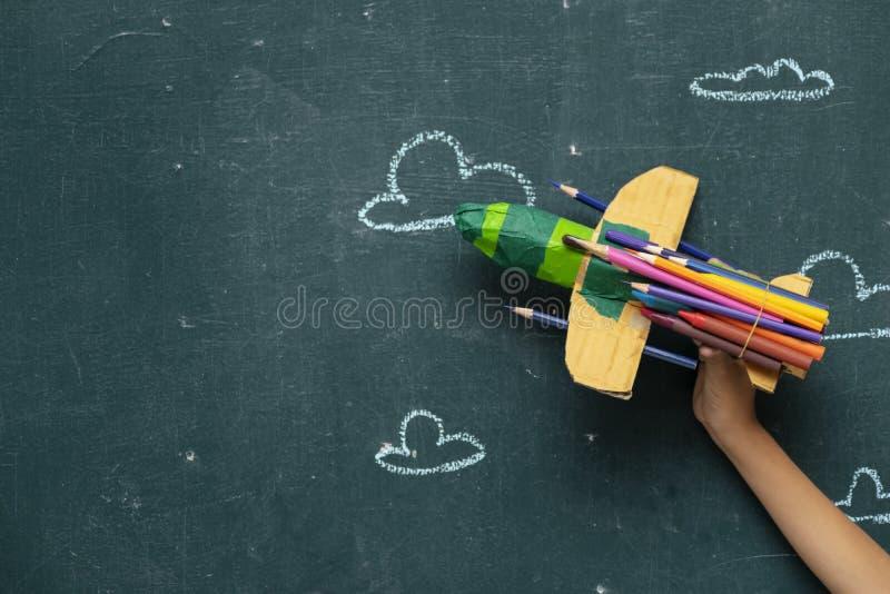 孩子的手拿着纸火箭 库存照片
